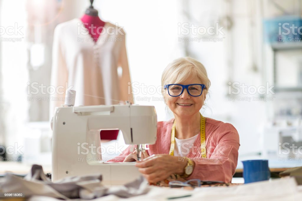 Senior fashion designer using a sewing machine in her workshop stock photo