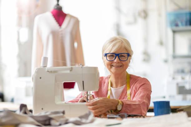 Senior-Mode-Designer mit einer Nähmaschine in ihrem Atelier – Foto