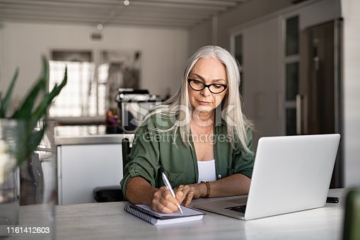 istock Senior fashionable woman working at home 1161412603