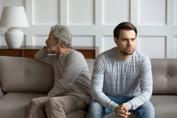 Senior father and adult son avoid talking after fight Upset stubborn young man and elderly father sit separately on couch at home avoid talking after fight, offended mad mature dad have misunderstanding with adult grown-up son, generation gap concept avoidance stock pictures, royalty-free photos & images