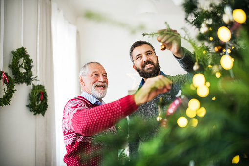A senior father and adult son decorating a Christmas tree.
