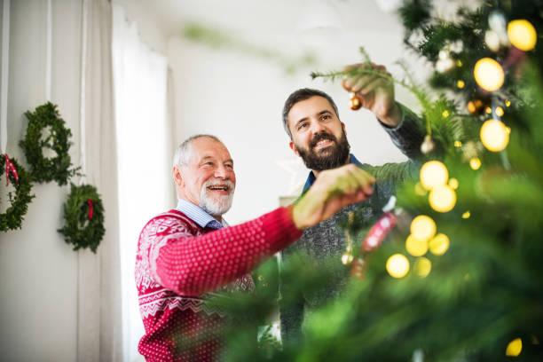 ein senior vater und erwachsener sohn einen weihnachtsbaum schmücken. - alte weihnachtsbäume stock-fotos und bilder