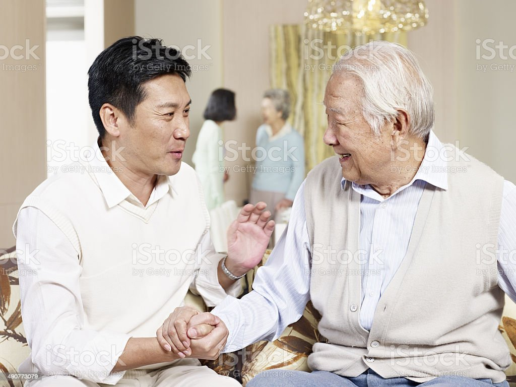 senior father and adult son stock photo