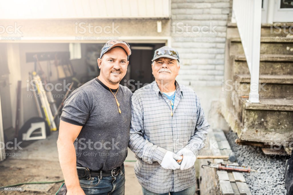 Senior father and his adult son renovating their house stock photo