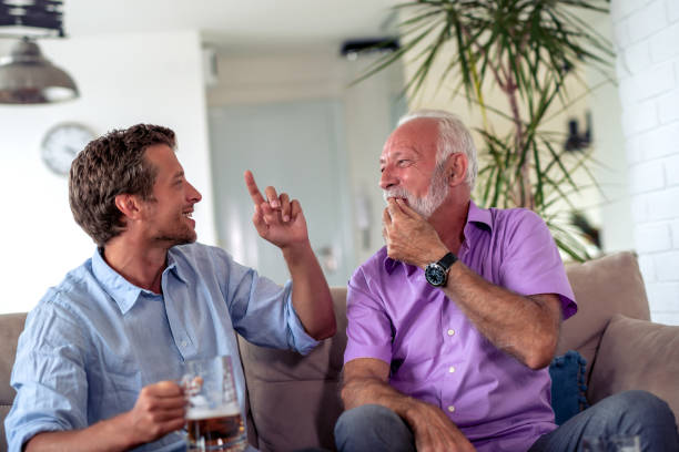 Senior father and his son watching football stock photo