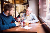 istock Senior father and his young son in a cafe. 888855824