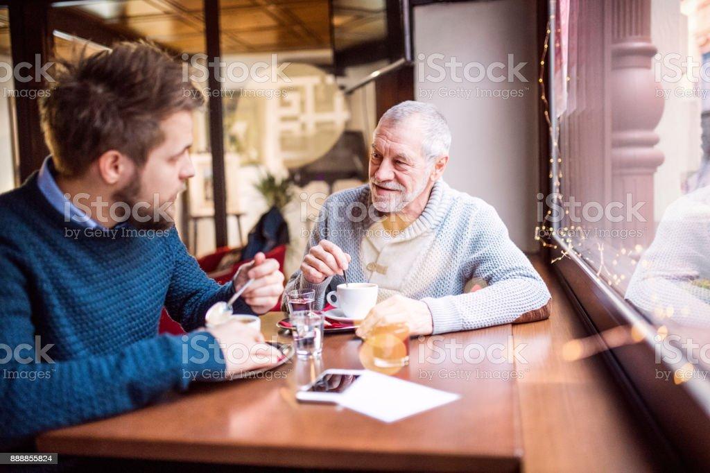 Pai sênior e seu filho em um café. - foto de acervo
