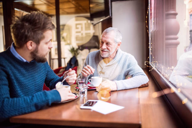 Senior father and his young son in a cafe. stock photo