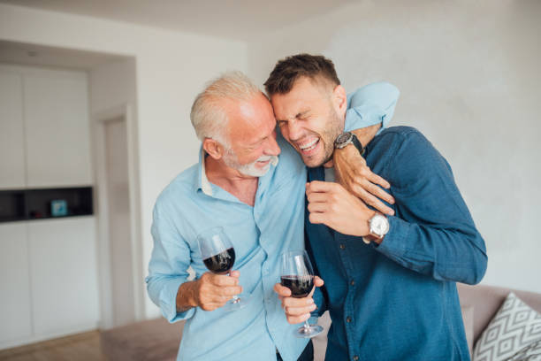 Senior father hugging adult son stock photo
