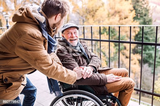 istock Senior father in wheelchair and young son on a walk. 892779842