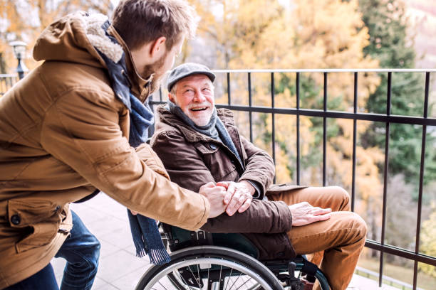 Senior father in wheelchair and young son on a walk picture id892779842?b=1&k=6&m=892779842&s=612x612&w=0&h=95etsqde6iumw9cbkpmz3y vq9ntl16rch1lwxq2jry=