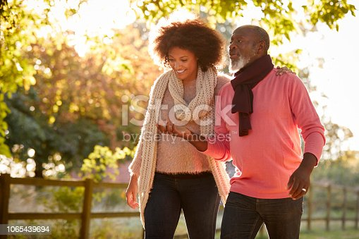 istock Senior Father With Adult Daughter Enjoying Autumn Walk In Countryside Together 1065439694