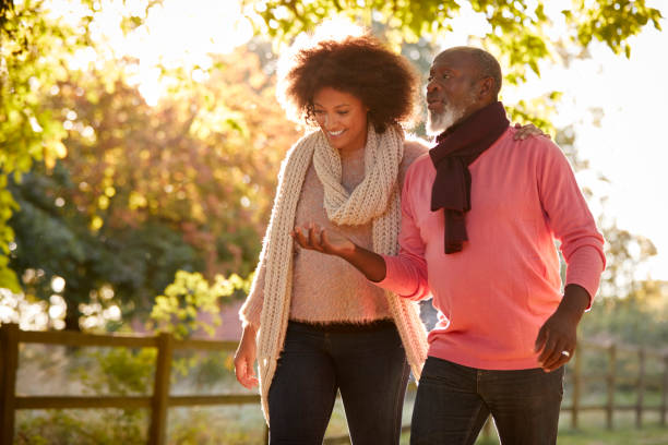 senior father with adult daughter enjoying autumn walk in countryside together - filhos adultos imagens e fotografias de stock