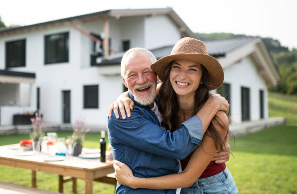 Senior father with daughter outdoors in backyard, looking at camera. stock photo