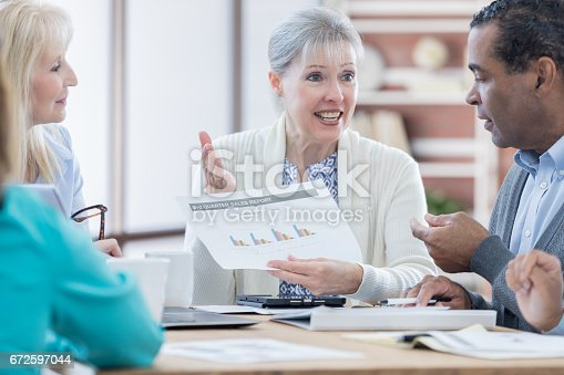 487670635istockphoto Senior female accountant discusses financial items during meeting 672597044