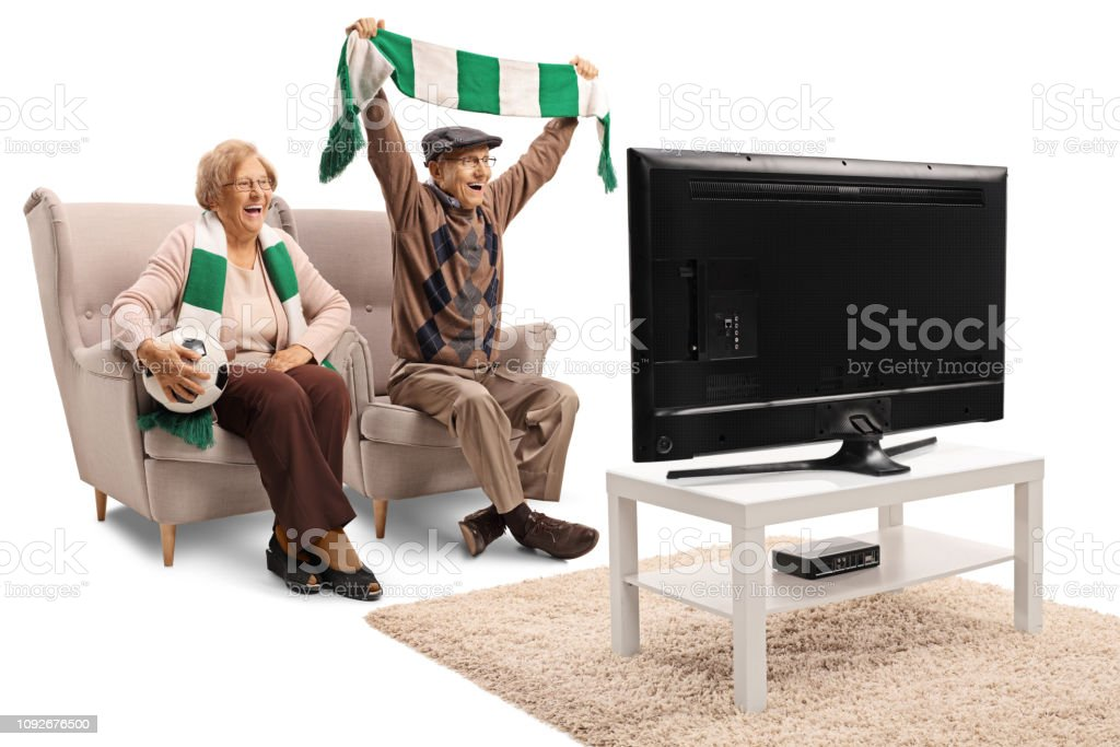 Senior female and male soccer fans cheering with a scarf and watching...