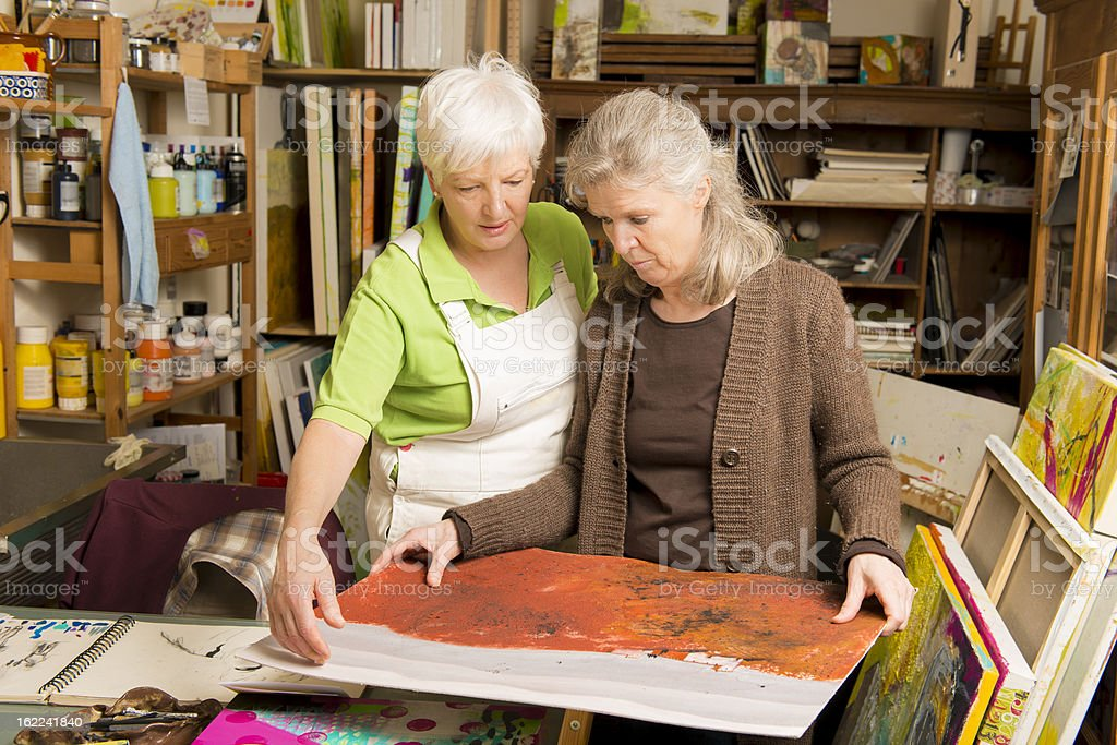 Senior female artist talking to woman showing painting royalty-free stock photo
