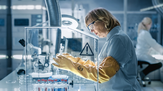 istock Senior Female Biologist Works with Samples in Isolation Glove Box. She's in a Modern, Busy Laboratory Equipped with State of the Art Technology. 949947312