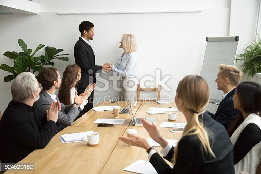 istock Senior female boss promoting handshaking african employee while team applauding 924520162