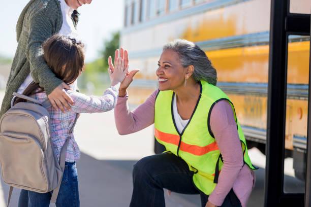 seniorende busfahrerin high-fives eine neue studentin - hausmeister stock-fotos und bilder