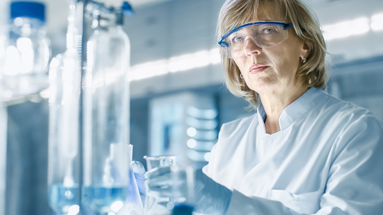 istock Senior Female Chemist in Safety Glasses Mixes Smoking Liquids in a Beakers. She Works in a Bright Modern Laboratory. 949947320