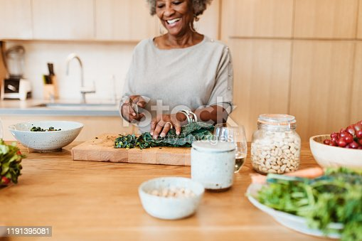 Smiling retired woman preparing meal in kitchen. Senior female is chopping vegetable at kitchen island. She is having frizzy gray hair.