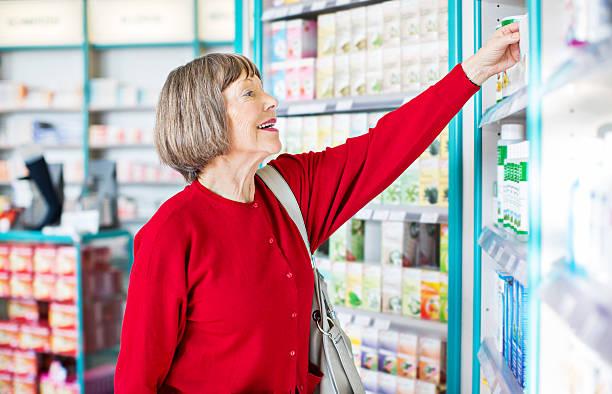 senior female customer buying medicine - lieblingsrezepte stock-fotos und bilder