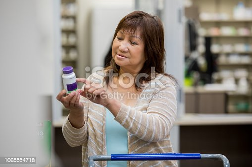 istock Senior female customer reading side effects of medicine in pharmacy 1065554718