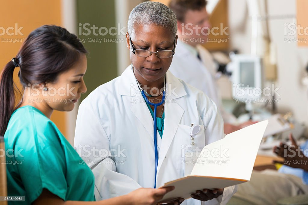 Senior female doctor reviewing patient chart with nurse in hospital stock photo