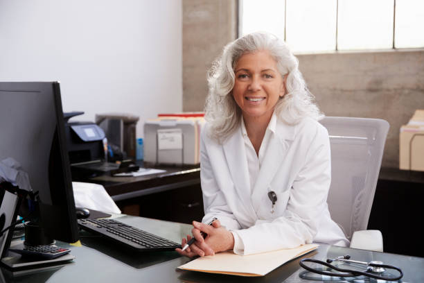 Senior female doctor sitting at desk in an office, portrait Senior female doctor sitting at desk in an office, portrait medium length hair stock pictures, royalty-free photos & images