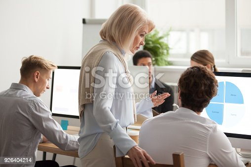 926404274 istock photo Senior female executive mentor supervising computer work of young intern 926404214