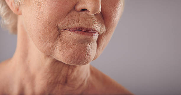 Senior female face with wrinkled skin Macro of a senior female face with wrinkled skin against grey background. Cropped old woman face. wrinkled stock pictures, royalty-free photos & images