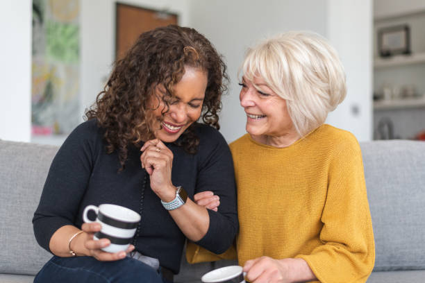 Senior female friends having tea Two senior women are spending time together. The friends are seated next to each other indoors. They are holding cups of coffee. One woman is caucasian and the other woman is black. The friends are embracing and laughing. baby boomers stock pictures, royalty-free photos & images