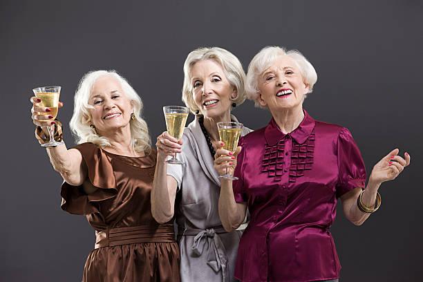 senior weiblich freunden anstoßen mit champagner - 70 jahre kleidung stock-fotos und bilder