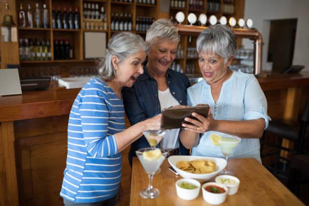 Senior female friends using digital tablet while having drinks stock photo