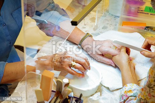 Senior Female getting her nails filed with a plastic divider put between her and the manicurist to prevent covid spread.