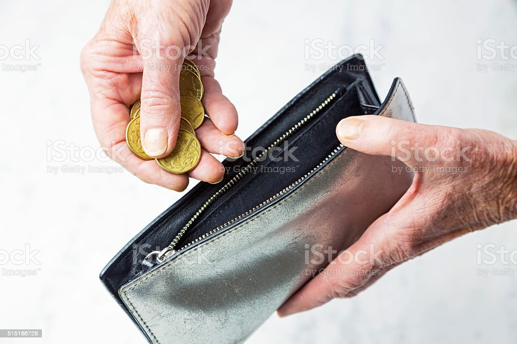 Senior female hand placing Australian coins in empty purse stock photo