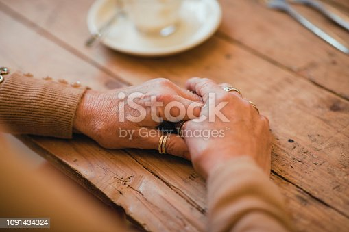 Close-up of a unrecognisable senior woman hands clasped on a table.