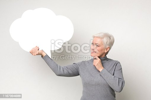 Pensive senior woman looking at blank speech bubble, touching her chin, copy space