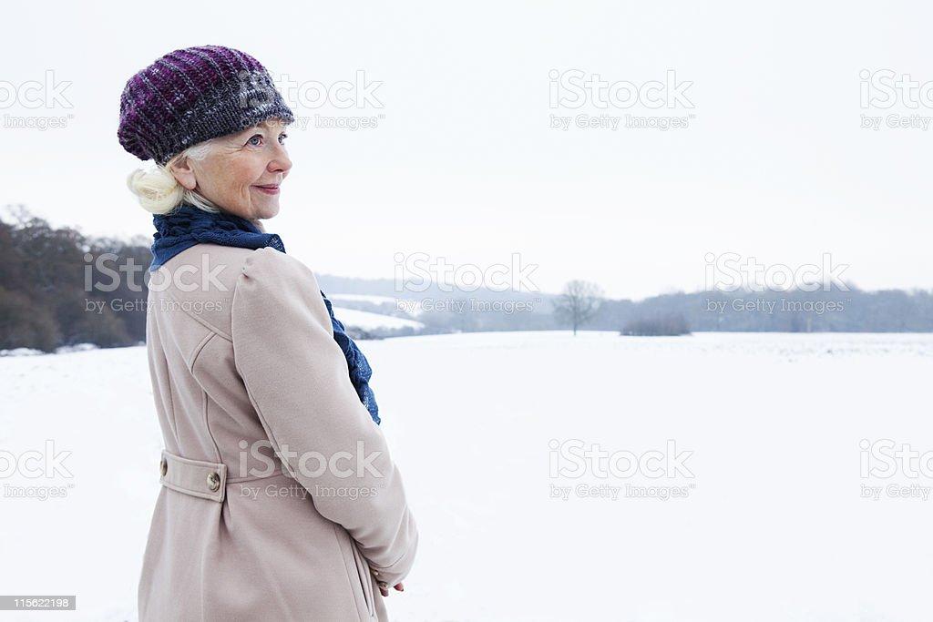 A senior female in a snowy landscape stock photo