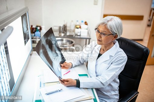 Female Japanese doctor seated in her office and examining x-ray imagery before deciding on a diagnosis.