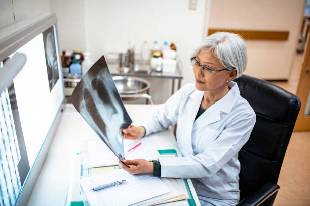 Senior Female Japanese Physician Studying X-Ray Imagery Female Japanese doctor seated in her office and examining x-ray imagery before deciding on a diagnosis. x ray equipment stock pictures, royalty-free photos & images