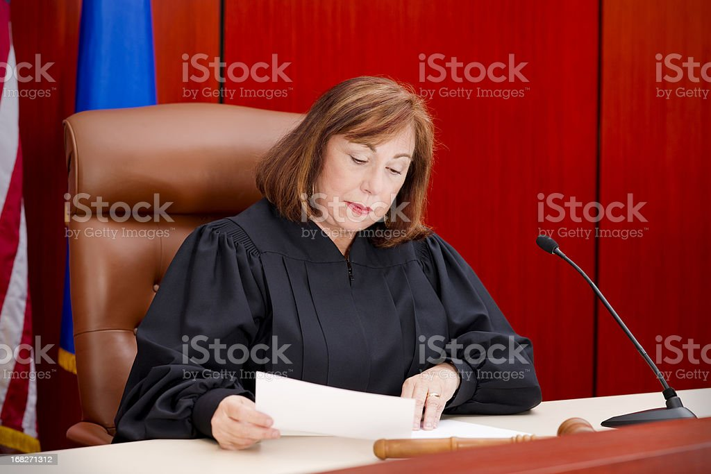 Senior female judge at the bench reading paper stock photo