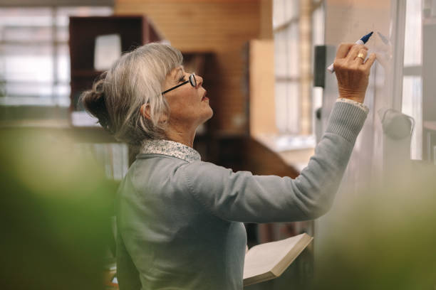 senior female lecturer writing on board - professore foto e immagini stock