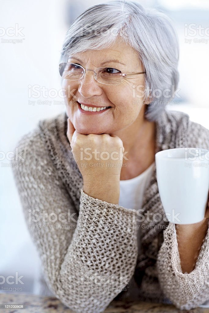 Senior female looking at something interesting with coffee royalty-free stock photo