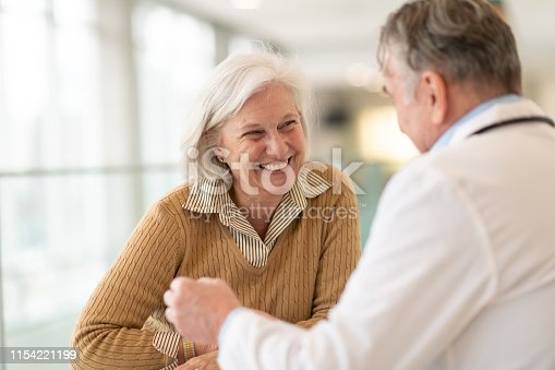A senior female patient is meeting with her doctor. The two are seated at a table together in a medical clinic. The patient is smiling warmly at her care provider. The male doctor is talking.