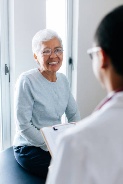 Senior female patient consulting at doctor's stock photo