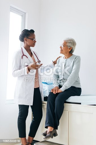 A senior female patient sitting on a consulting bed and listening to a young female doctor standing next to her.