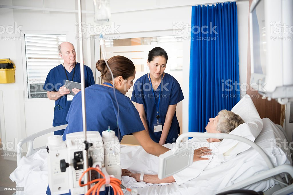 Senior female patient in bed with concerned medical staff stock photo