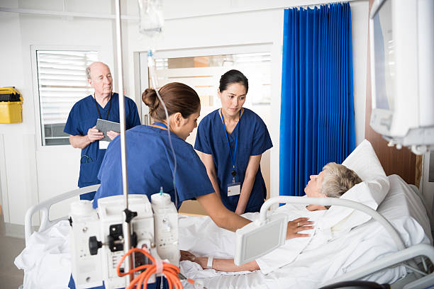 senior female patient in bed with concerned medical staff - australian nurses stock photos and pictures